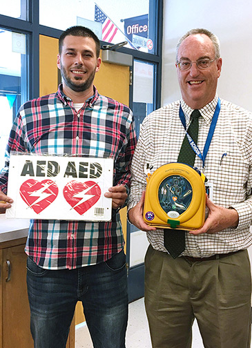 Mr. Poulsen donates an AED to T.H. Bell and Principal Ward accepts the AED.